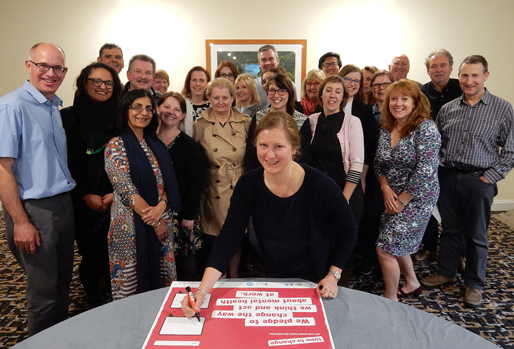 Voluntary Arts staff and board signing the Time to Change pledge card