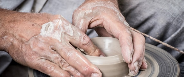 Mans hands using pottery wheel